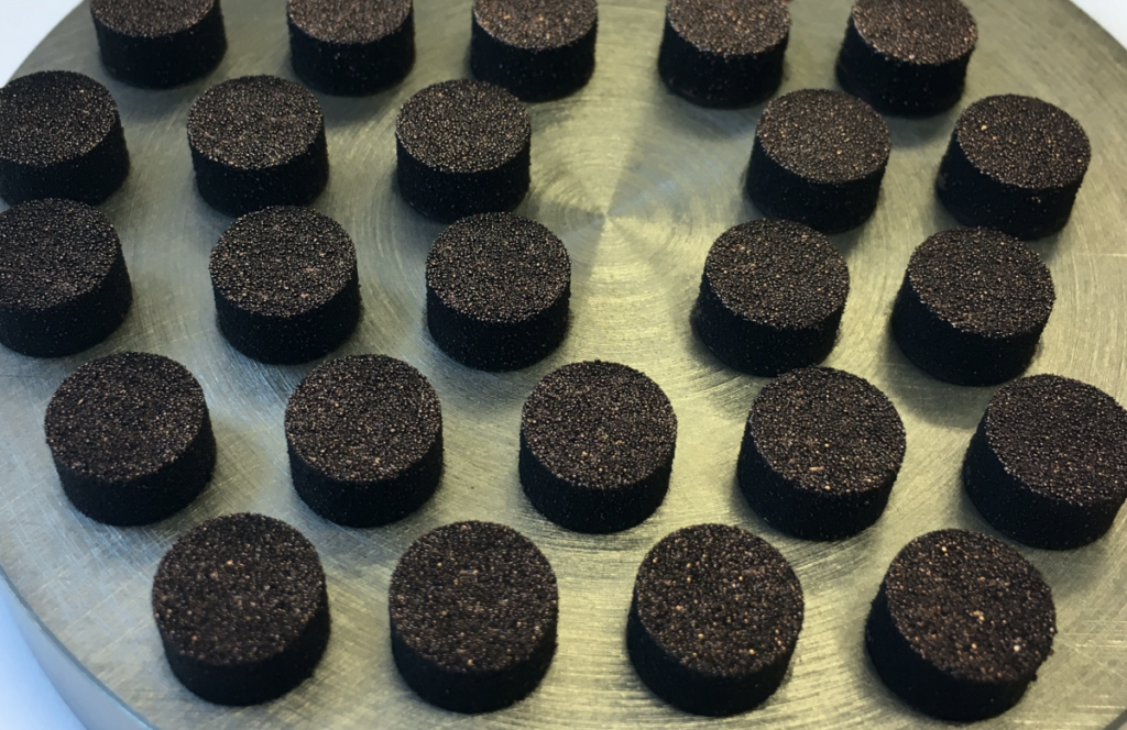 Dark coloured graphene coated copper tablets on a metal scale during testing.